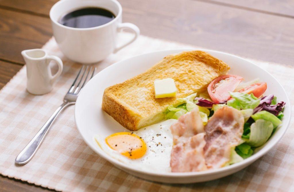 皿の上のサンドイッチとコーヒー  自動的に生成された説明