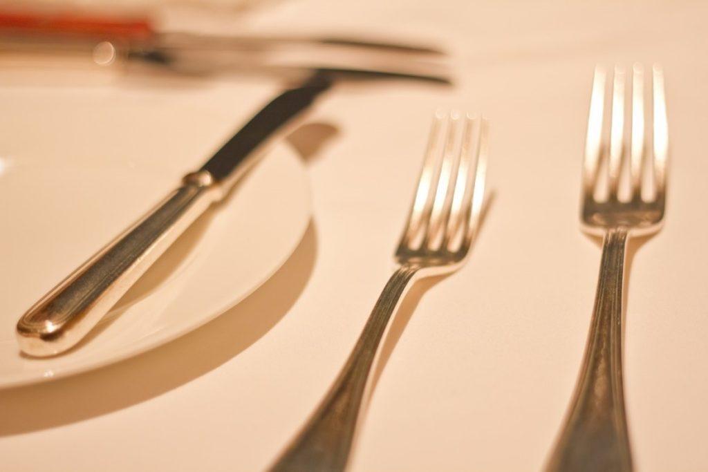 皿の上に置かれたフォーク  自動的に生成された説明